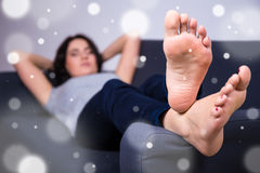 Winter relaxation concept - woman lying on sofa at home Royalty Free Stock Image