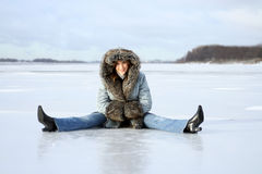 Winter rest. Young woman sits on the ice Stock Photo