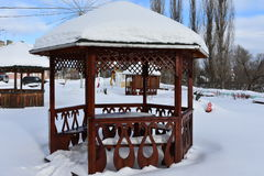 Winter the resting place of the gazebo. Place relaxation gazebo carved furniture handrails on the background of poplars stock photos