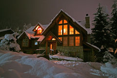 Winter Retreat. A winter home in Whistler, BC blanketed by a fresh dumping of snow. Slightly grainy, but warm royalty free stock photo