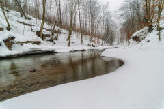 Winter river in the Carpathian Mountains with snow-covered banks Stock Images