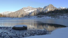 Winter river flowing to frozen mountain lake in italian alps stock video footage