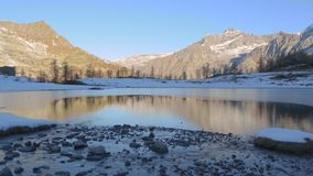 Winter river flowing to frozen mountain lake in italian alps stock video