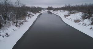 Winter river landscape. Aerial view winter river with snow-covered shore. Flight over the river in winter in the countryside. Aerial footage stock video footage