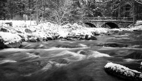 Winter river landscape with stone bridge black and white. Black and white winter river landscape with stone bridge in background Royalty Free Stock Photo