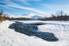 Winter river in the north of Sweden with mountains in background Stock Photo