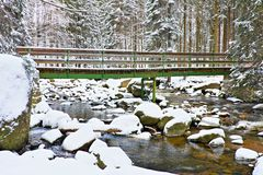 Winter at river and old footbridge. Big stones in stream covered with fresh powder snow and lazy water with low level. Stock Images