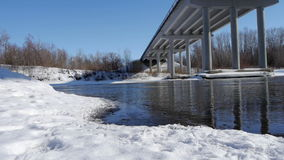Winter river with open water under the bridge stock video