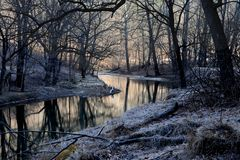 Winter river that reflect late afternoon sun light, zigzagging along leafless woods stock photography