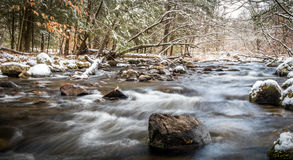 Winter river scene in the forest with snow. Winter river scene in the forest with dreamy river flowing among snowy rocks Stock Image