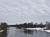 Winter river and snow against a blue sky with clouds royalty free stock image