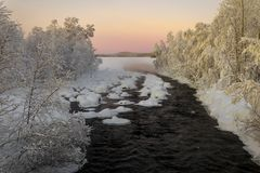 Winter river, surrounded by trees, in Finland at sunset Stock Image