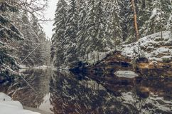 Winter by the river. With steep banks, calm flow and snowy forest Stock Photo