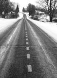 Winter road. Black and white picture of the country road in winter, focus on dividing line Stock Photos