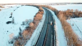 Winter road. Aerial view landscape. Winter sunset road. Passing cars, trucks. Aerial view landscape stock footage