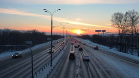 Winter road with cars at sunset. Beautiful horizon in dusk backlit with sun. stock video footage