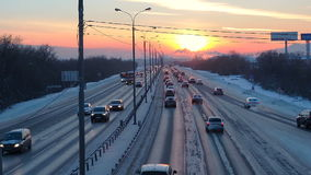 Winter road with cars at sunset. Beautiful horizon in dusk backlit with sun. stock video