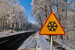 Winter road, driving through snowy forest, warning sign Royalty Free Stock Image