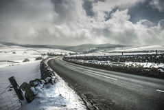 Winter Road. Empty road in winter landscape through the Peak District with dramatic sky and snow Stock Photography