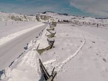 Winter road and fence in Idaho. Winter snow covered landscape with fence running along a road stock footage