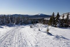 Winter road in forests and mountains.Taiga.Russia. Royalty Free Stock Photography
