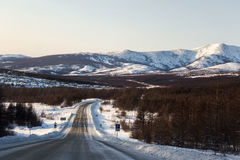 Winter road, hills, Magadan. Winter road with mountain landscape, Magadan Stock Photo
