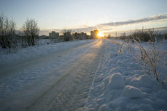 Winter road leading to the house at sunset. Stock Photography