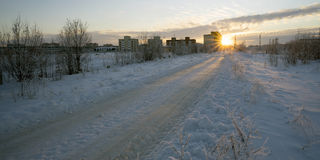 Winter road leading to the house at sunset. Royalty Free Stock Photography