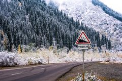 Winter road in the mountains and a road sign Stock Photo