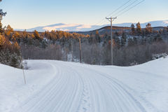 Winter road with the power line at the side. Narrow road with power line on the side. beautiful scenery with forest and mountain Stock Image