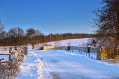 Winter road. Route running along the idyllic countryside in the late afternoon royalty free stock photo