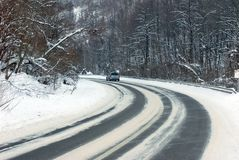 Winter road. Snow covered trees lining road receding into distance, winter scene Stock Image