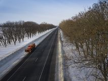 Winter Road snowing in winter season. Snowblower cleans the road. Aerial. Winter Road snowing in winter season stock photos