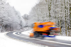 Winter on the road, snowplow. Snowplow working on icy winter road, vehicle blurred Royalty Free Stock Images