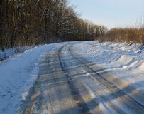 Winter road in snowy forest landscape Royalty Free Stock Image