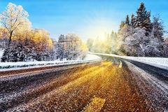 Winter road in sunlight. Winter road with sunlight reflecting on asphalt Stock Image