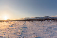 Winter road to the forest. Sunset landscape. Snow covered field. Stock Photo