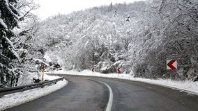 Winter road with trees covered with snow. Cleaned winter road with sand sprinkled on asphalt for better traction and trees and vegetation on both sides covered Royalty Free Stock Image