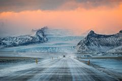 Winter Road Trip in Iceland. Driving down a road covered in ice as the arctic wind blows snow off the mountains stock photo