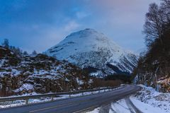 Winter road trough snow caped mountains in eastern norway. With a cloudy blue sky royalty free stock images