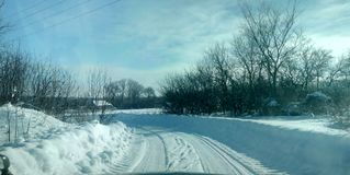 Winter road in village. Winter snowy rural road Royalty Free Stock Images