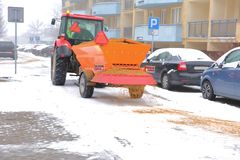 Tractor with an automatic trailer for spreading sand on roads. During winter, the roads are quite dangerous, because they are often sprinkled with sand, for royalty free stock photography