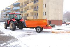 Tractor with an automatic trailer for spreading sand on roads. During winter, the roads are quite dangerous, because they are often sprinkled with sand, for stock photos