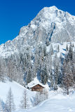Winter rock with fresh fallen snow on top and house. Royalty Free Stock Images