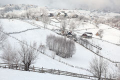 Winter in a Romanian mountain village with the Carpathians Stock Photos