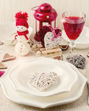 Winter romantic evening on Valentine's day. Valentine's day tabl. E setting with candles and decorations in the form of hearts Royalty Free Stock Images