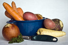 Root vegetables. Root vegetables in a casserole bowl, with peeler Royalty Free Stock Images