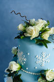 Winter Rose wedding cake. Detail of a romantic blue wedding cake decorated with hand made frosted sugar roses, snow christals and sugar christals, on a blue Royalty Free Stock Image