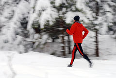 Winter running. Woman in orange tracsuit running in the forest, intentional motion blur Stock Images