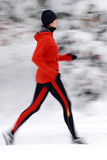 Winter running. Woman in orange tracsuit running in the forest, intentional motion blur royalty free stock image